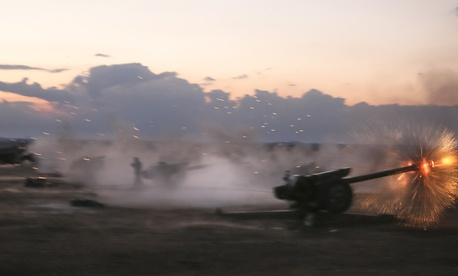 In this photo taken on Wednesday, Oct. 7, 2015, Syrian army howitzers fire near the village of Morek in Syria.