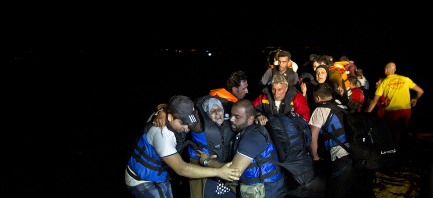 Two Syrian refugees try to carry an elderly woman off a dinghy as it arrives from the Turkish coast to the northeastern Greek island of Lesbos, Tuesday, Oct. 6 , 2015.