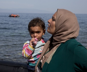 A dinghy full of migrants approaches the coast of the Greek island of Lesbos after crossing from Turkey to Greece as a Syrian woman who just arrive holds her child,Thursday, Sept. 10, 2015.