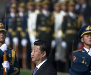 Chinese President Xi Jinping, center, walks past guard of honor while visiting the Monument to the People's Heroes during a ceremony marking Martyr's Day at Tiananmen Square in Beijing, China Wednesday, Sept. 30, 2015.