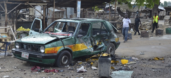 People walk past a damaged car at the site of a bomb explosion in Maiduguri, Nigeria, Friday, July 31, 2015.
