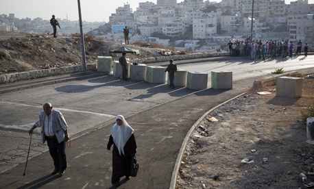 Israeli border police check Palestinian's IDs at a checkpoint as they exit the Arab neighborhood of Issawiyeh in Jerusalem, Sunday, Oct. 18, 2015.