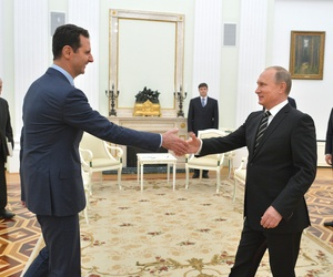 n this photo taken on Tuesday, Oct. 20, 2015, Russian President Vladimir Putin, right, shakes hand with Syrian President Bashar Assad in the Kremlin in Moscow, Russia.