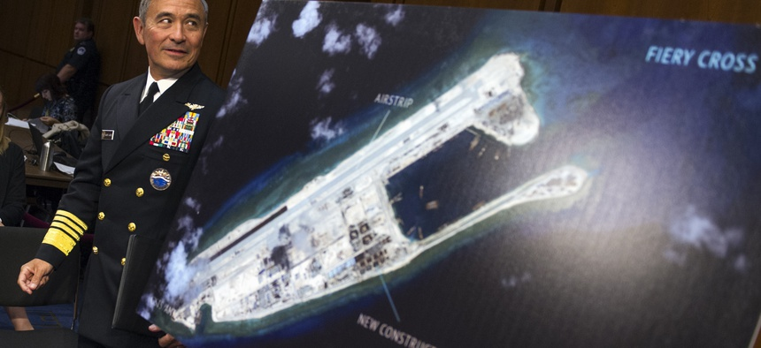 Adm. Harry B. Harris, Jr. of U.S. Navy Commander, U.S. Pacific Command walks past a photograph showing an island that China is building on the Fiery Cross Reef in the South China Sea, as the prepares to testify on Capitol Hill, Sept. 17, 2015.