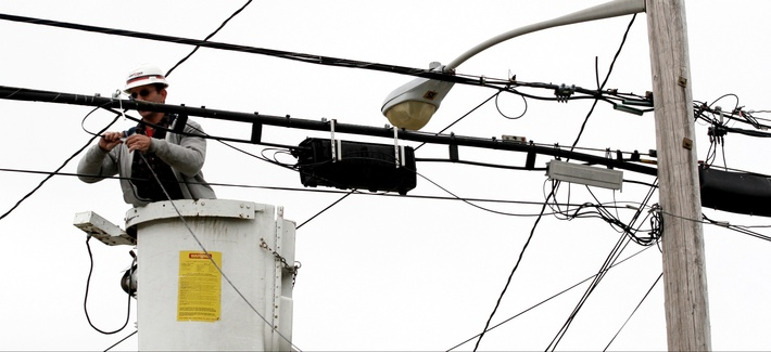Verizon lineman Joe DeBonis connects fiber optic cable that will serve a home in North Bellmore, N.Y. in a file photo from May 11, 2006.