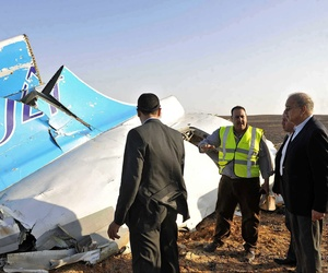 Egyptian Prime Minister Sherif Ismail, right, looks at the remains of a crashed Russian passenger jet in Hassana, Egypt.