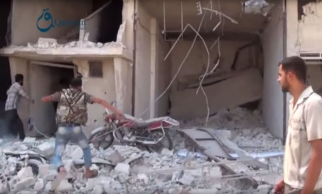 Syrians gather near the rubble of a building, in the aftermath of a Russian airstrike, in Dair al-Asafeer village, rural Damascus, Syria.