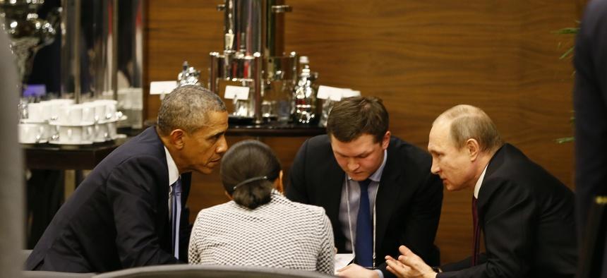 U.S. President Barack Obama, left, speaks with Russian President Vladimir Putin, right prior to the opening session of the G-20 summit in Antalya, Turkey, Sunday, Nov. 15 2015.