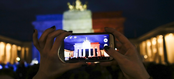 A woman takes a picture of the Brandenburg Gate, illuminated in the French national colors for the victims killed in the Friday's attacks in Paris, France in Berlin, Saturday, Nov. 14, 2015.
