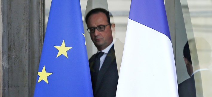 French President Francois Hollande is framed by the French flag, right, and the european flag as he walks through the lobby of the Elysee Palace after the weekly cabinet, in Paris, Wednesday, Nov.18, 2015.