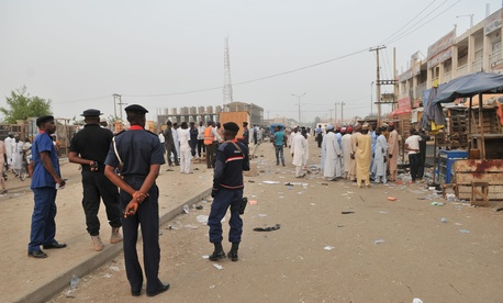 Security officers stand guard at the scene of an explosion at a mobile phone market in Kano, Nigeria.