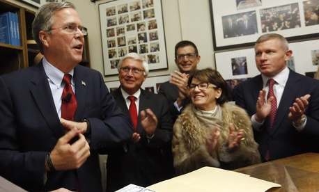 Gov. Jeb Bush cheers with supporters after filing papers to be on the nation's earliest presidential primary ballot, Thursday, Nov. 19, 2015, in Concord, N.H.