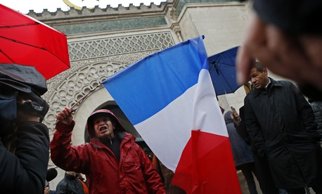 "A French Muslim, of Algeria origin, who wants to be named ""Cherif"" talks to the media, holding a French flag, in front of the Great Mosque of Paris after the Friday priest, in Paris, France, Friday, Nov. 20, 2015 one week after the Paris attacks."