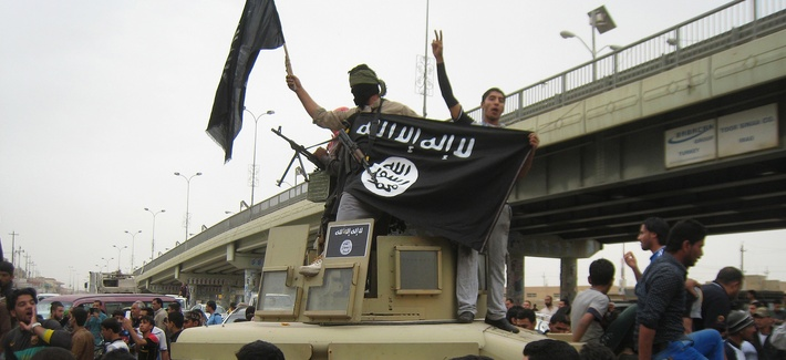 In this Sunday, March 30, 2014, file photo, Islamic State group militants hold up their flag as they patrol in a commandeered Iraqi military vehicle in Fallujah, 40 miles (65 kilometers) west of Baghdad, Iraq.