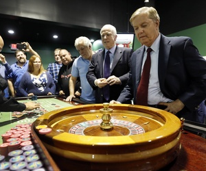 Republican presidential candidate Sen. Lindsey Graham, R-S.C., right, watches as he and Sen. John McCain, R-Ariz., play the roulette wheel at a charitable gaming poker room during a campaign stop at the Manchester Bingo Center and Poker Room Oct. 9, 2015.