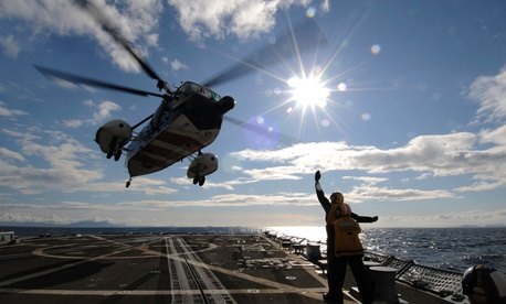 ATLANTIC OCEAN (April 23, 2012) Seaman Apprentice Pedro Deleon, front, communicates to the pilots of a Royal British navy helicopter using hand signals as they take off from the flight deck aboard the guided-missile destroyer USS Forrest Sherman (DDG 98).