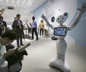 In this June 6, 2014 file photo, journalists surround humanoid robot Pepper on display at SoftBank Mobile shop in Tokyo. Japanese mobile carrier Softbank said Tuesday, Feb. 10, 2015.
