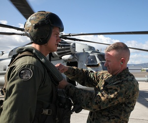 Brig. Gen. Eric M. Smith pins a Navy Achievement Medal on Sgt. Steven A. Meyer, a CH-53 Super Stallion crew member with Special Purpose Marine Air-Ground Task Force-Southern Command.