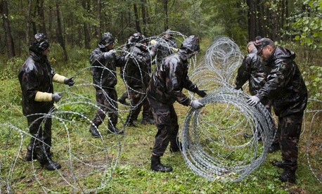 Hungarian soldiers extend spools of razor wire on Slovenian border in Zitkovci, Friday, Sept. 25, 2015.