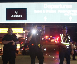 Officers stand at the entrance to New Orleans International Airport, Friday, March 20, 2015, in Kenner, La.