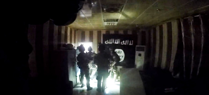U.S. and Iraqi special forces search for enemy fighters and free dozens of hostages from a makeshift prison in Huwija, Iraq, in this image from helmet cam video taken Oct. 22, 2015.