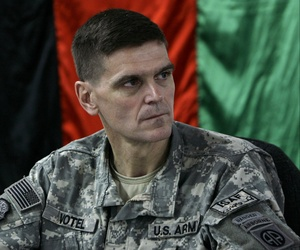 U.S. Brig. Gen. Joseph Votel listens in front of an Afghan national flag during a meeting with Afghan officials in an Afghan military base in Kabul, Afghanistan Sunday, Feb. 24, 2007.