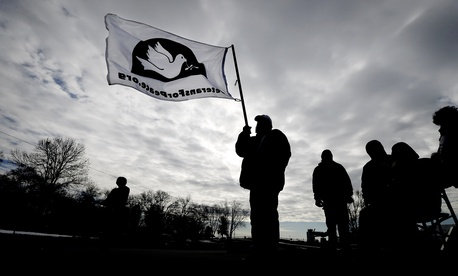 Allen Burney, of Des Moines, Iowa, waves a Veterans for Peace flag during a protest against drone strikes at the Iowa Air National Guard base, Monday, March 17, 2014, in Des Moines, Iowa.