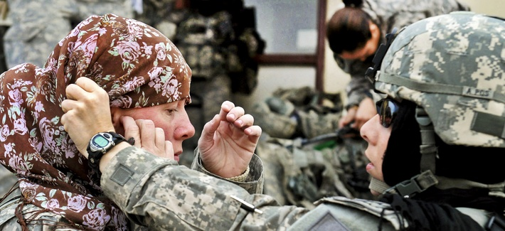 U.S. Army Maj. Rosemary Reed of the Khowst Provincial Reconstruction Team helps U.S. Army Sgt. 1st Class Paula Reill of the 3-19th Indiana Agricultural Development Team with her head scarf.