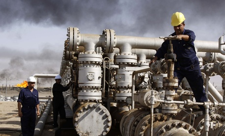 Iraqi laborers work at the Rumaila oil refinery in Zubair near the city of Basra, Iraq, in a 2009 file photo.