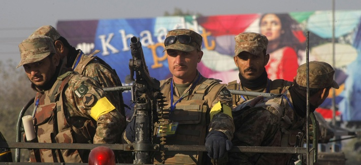 Pakistani army soldiers patrol outside the army public school during a ceremony in connection with first anniversary of the school attack in Peshawar, Pakistan, Wednesday, Dec. 16, 2015.