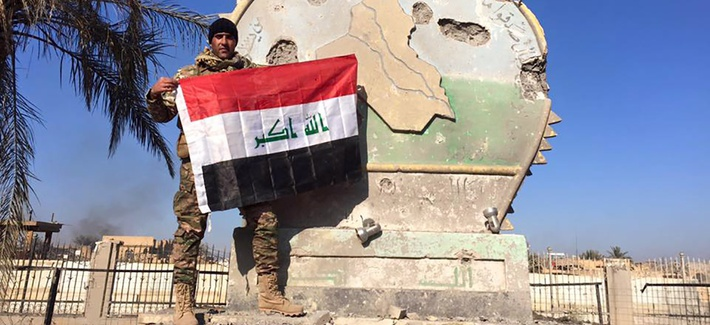 An Iraqi soldier holds a national flag in the government complex in central Ramadi, 70 miles (115 kilometers) west of Baghdad, Iraq, Monday, Dec. 28, 2015.