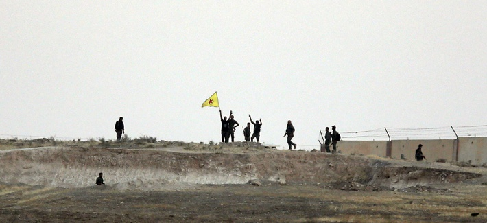 In this photo taken from the Turkish side of the border between Turkey and Syria, in Akcakale, southeastern Turkey, Kurdish fighters with the Kurdish People's Protection Units, or YPG, wave their yellow triangular flag.