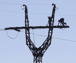 Workers repair an electricity power line damaged during shelling near a power station outside the city of Slovyansk, Donetsk Region, eastern Ukraine Thursday, July 10, 2014.