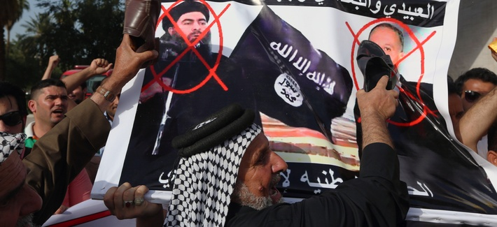 Protesters carry defaced posters of Islamic state leader Abu Bakr al-Baghdadi and Iraqi Defence Minister Khaled al-Obeidi as they chant slogans against the Islamic State group during a protest at Tahrir Square in Baghdad, Iraq, April, 2015.