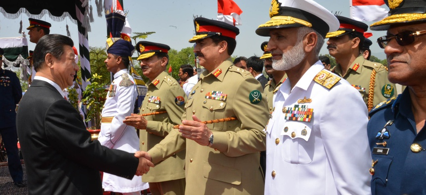 In this April 20, 2015, file photo provided by Pakistan's Press Information Department, Chinese President Xi Jinping, left, shakes hands with Pakistan's army chief Gen. Raheel Sharif, at Nur Khan airbase in Islamabad, Pakistan.