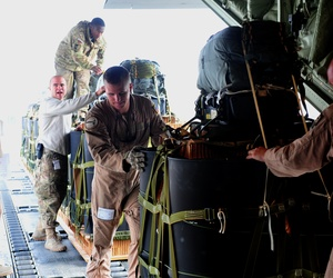 Air Force and Army personnel use a K-loader to load the Joint Precision Air Drop system bundles onto a C-130J Hercules, Bagram AF, Afghanistan, Nov. 27, 2011.