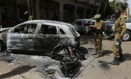 Soldiers take notes on a car that was burnt out outside the Splendid Hotel in Ouagadougou, Burkina Faso, Sunday, Jan. 17, 2016.