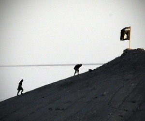 ISIS fighters place their group's flag on a hilltop east of Kobani, Syria, Oct. 6, 2014. Coalition airstrikes and a Kurdish assault would clear them from Kobane two months later.