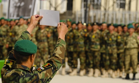 An Afghan National Army soldier holds up his diistinguished graduate certificate during the 3rd term graduation oath ceremony at Ghazi Military Training Center in Kabul, Afghanistan.