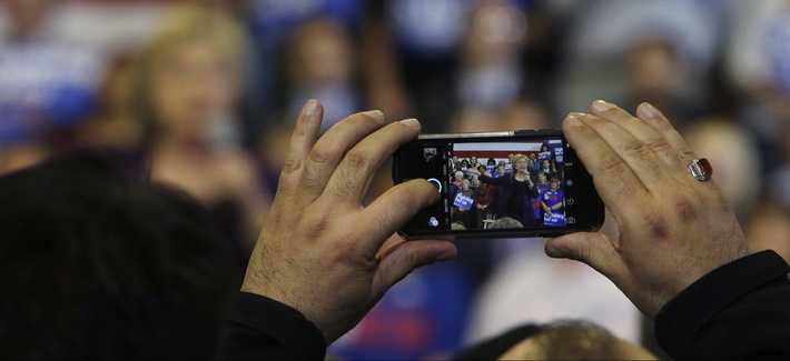 A potential voter takes a photo as Democratic presidential candidate Hillary Clinton speaks at a campaign event, Tuesday, Feb. 2, 2016, in Nashua, N.H.