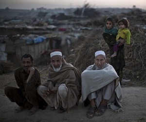 Pakistani men, who were displaced with their families from Pakistan's tribal areas due to fighting between the Taliban and the army, sit on a roadside on the outskirts of Islamabad, Pakistan, Saturday, Nov. 2, 2013.