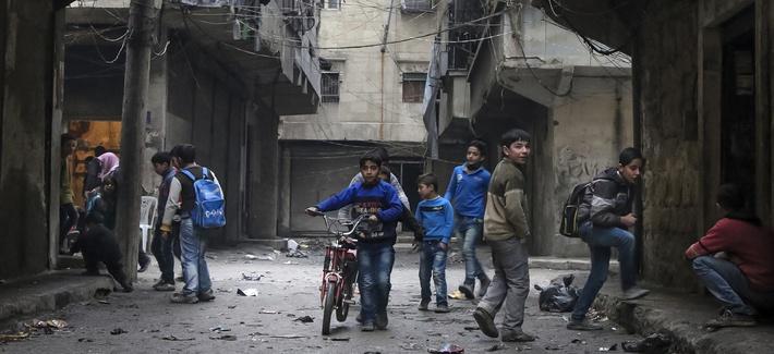 In this Thursday, Feb. 11, 2016 photo, school boys play in a street in Aleppo, Syria.