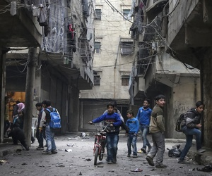 In this Thursday, Feb. 11, 2016 photo, school boys play in a street in Aleppo, Syria.
