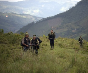 In this Jan. 3, 2016 photo, members of the 36th Front of the Revolutionary Armed Forces of Colombia or FARC, trek to a new camp in Antioquia state, in the northwest Andes of Colombia.