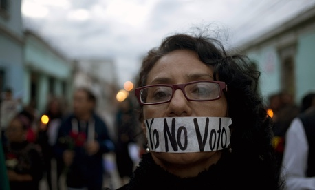 "A demonstrator covers her mouth with tape carrying the message Spanish: ""I'm not voting,"" during a protest demanding election reform in Guatemala City, Saturday, Sept. 5, 2015, the day before general elections."