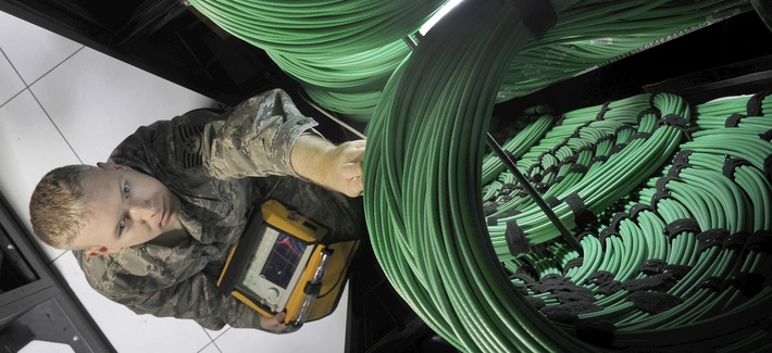 A U.S. Air Force cyber-transport technician checks network routers at the Defense Media Activity's Headquarters at Fort Meade, Md., July 18, 2012.