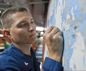A U.S. sailor reviews a map aboard the Ticonderoga-class guided-missile cruiser USS Cape St. George (CG 71), July 28, 2012.