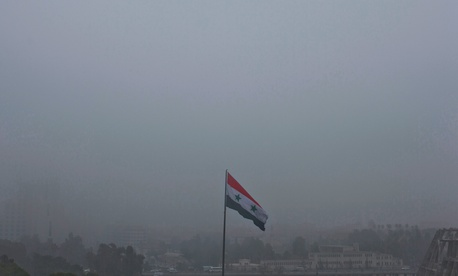A Syrian national flag waves as heavy fog envelops the capital city of Damascus, Syria, Wednesday, Feb. 24, 2016.