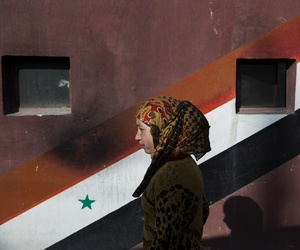 In this Thursday, March 3, 2016 photo, a woman passes a painting of Syrian flag in At-Tall, a town of northern outskirts of Damascus, Syria.
