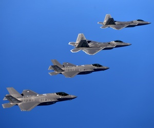 F-22 Raptors from the 94th Fighter Squadron and F-35A Lightning IIs fly in formation after completing a training mission.